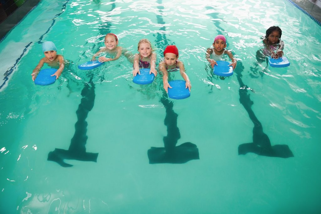 Kids swimming in a pool with green water