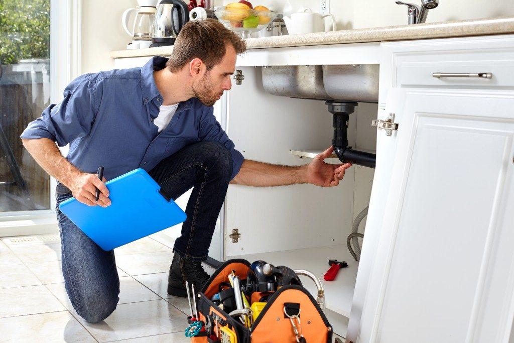 Plumber checking sink pipe