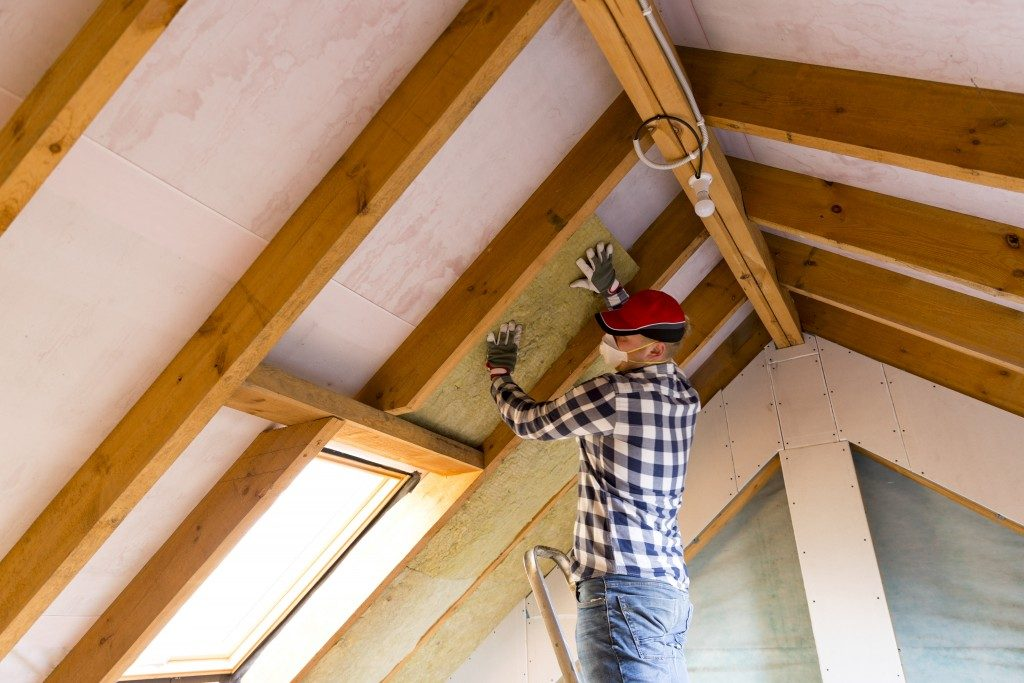 COnstruction worker installing ceiling wood
