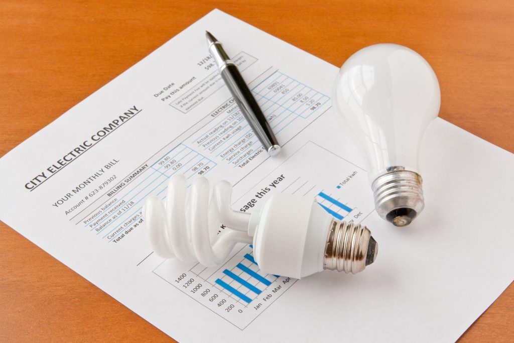 Electricity bill with light bulb and pen on top