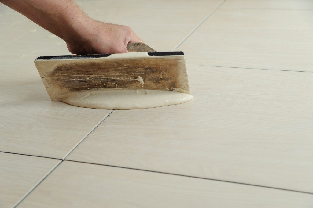 Worker filling tiles with grout