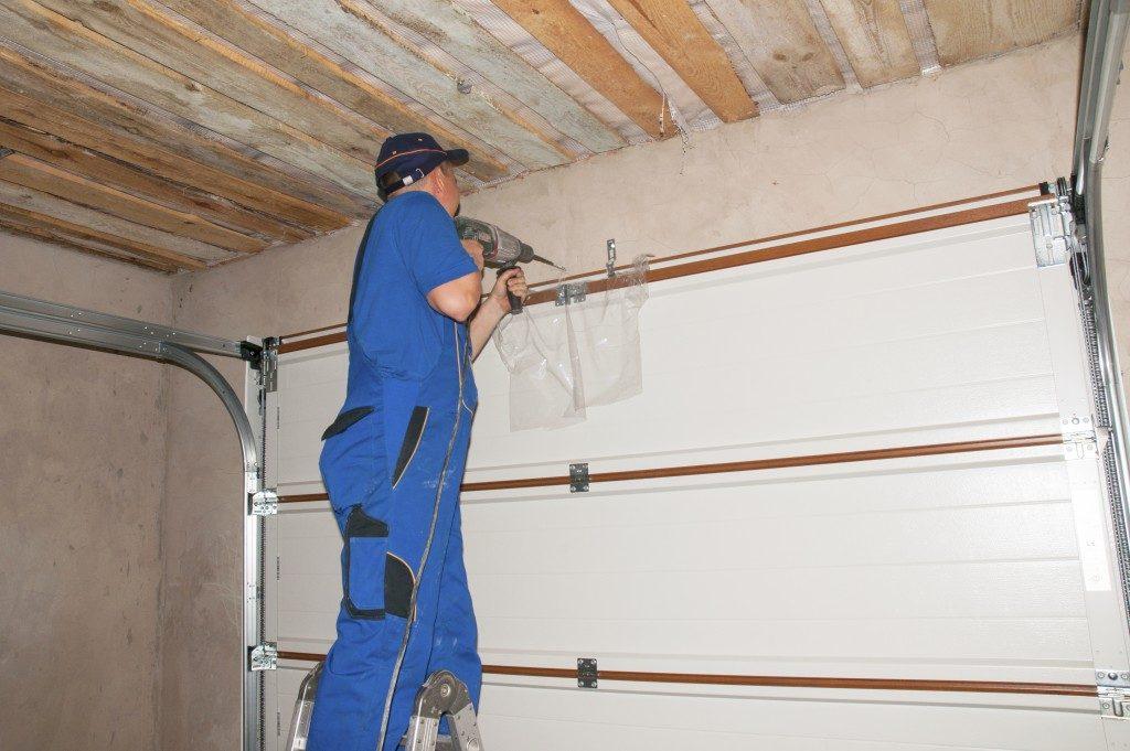 Worker repairing the garage door