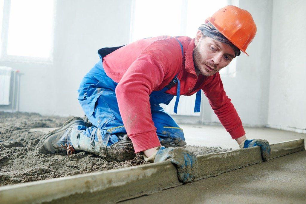 man constructing concrete flooring