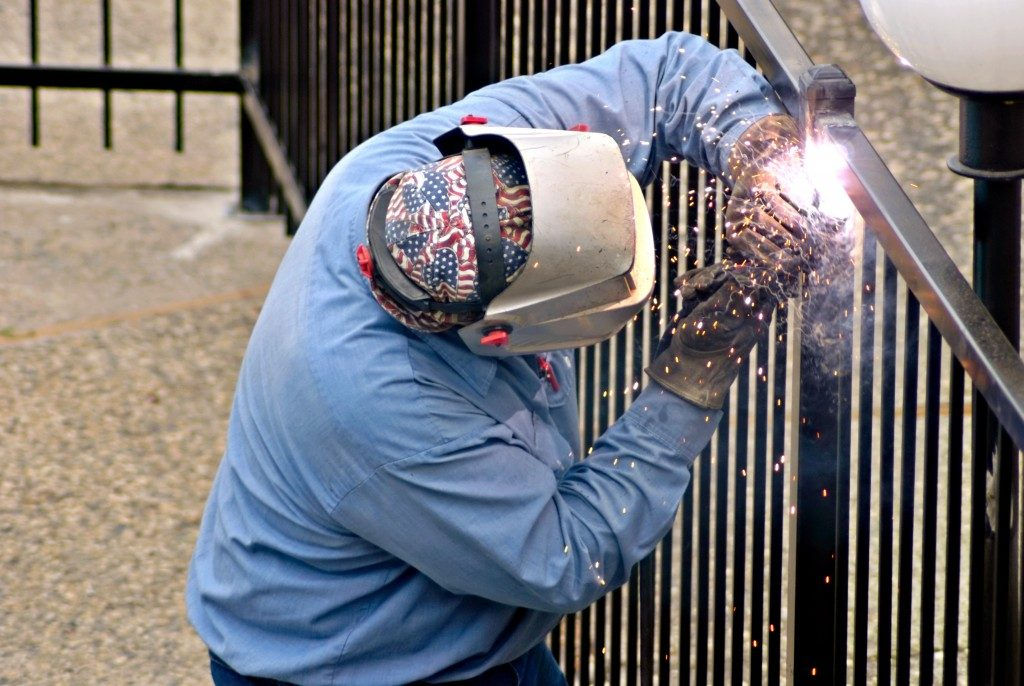 worker installing a metal fence