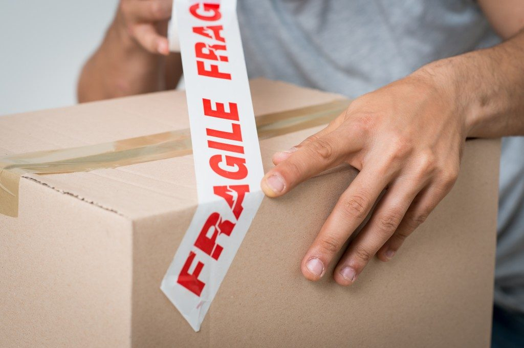 Man putting a fragile tag on the box