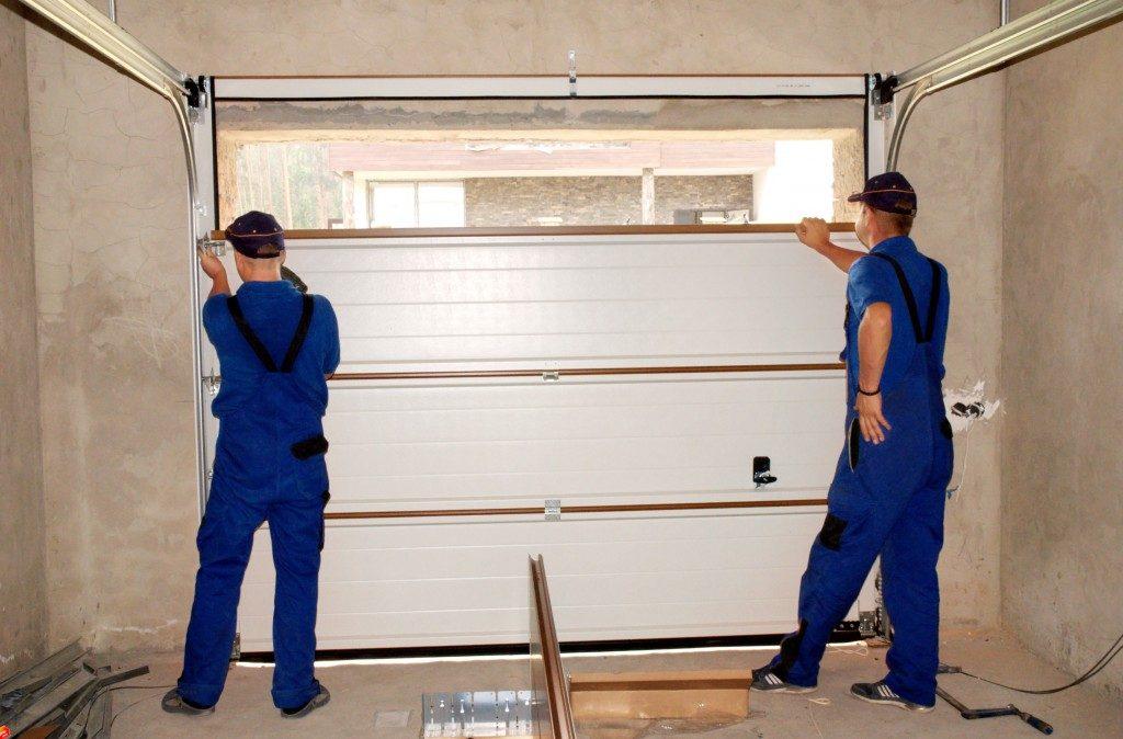 two men installing a garage door