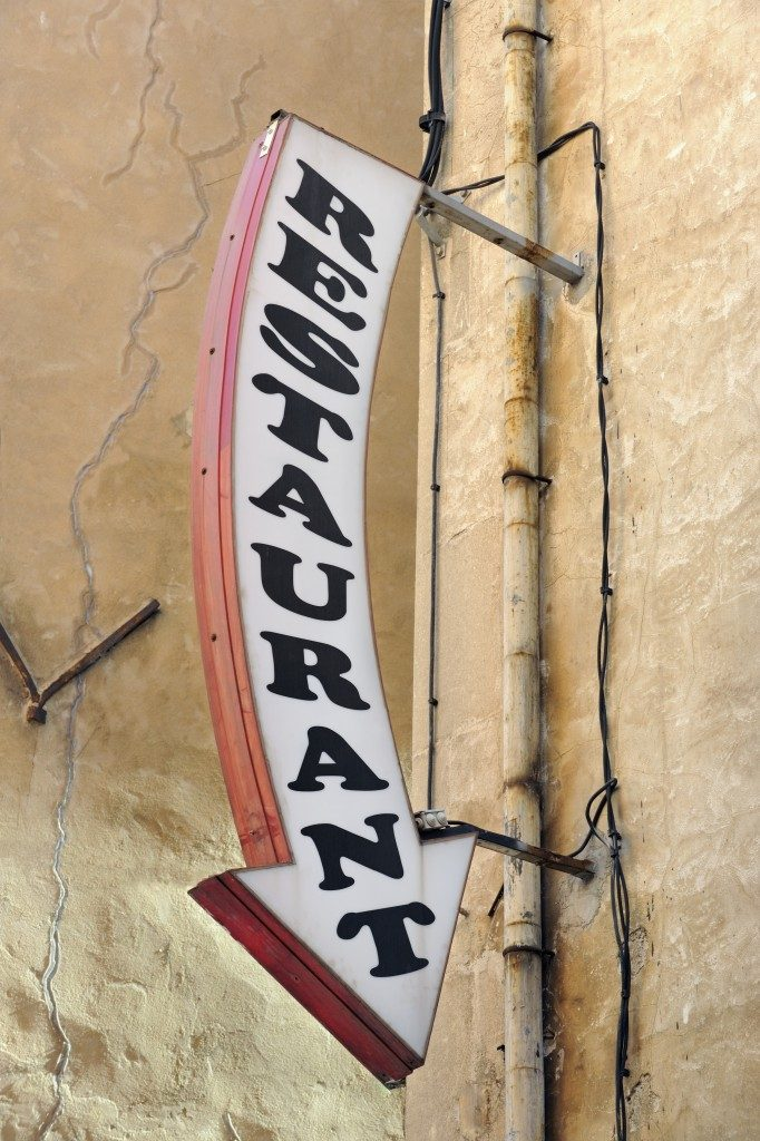 Restaurant arrow sign, black writing on white background, with ochre painted wall behind