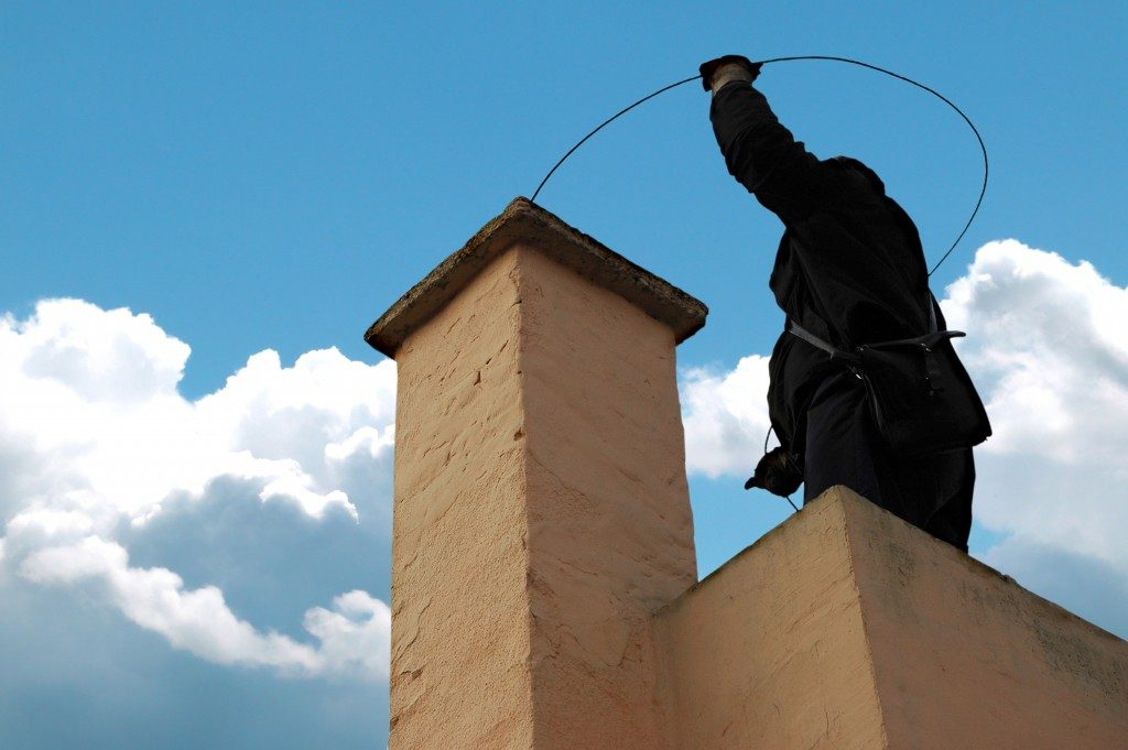 Chimney sweeper on the roof of a house in an attempt of chimney sweeping