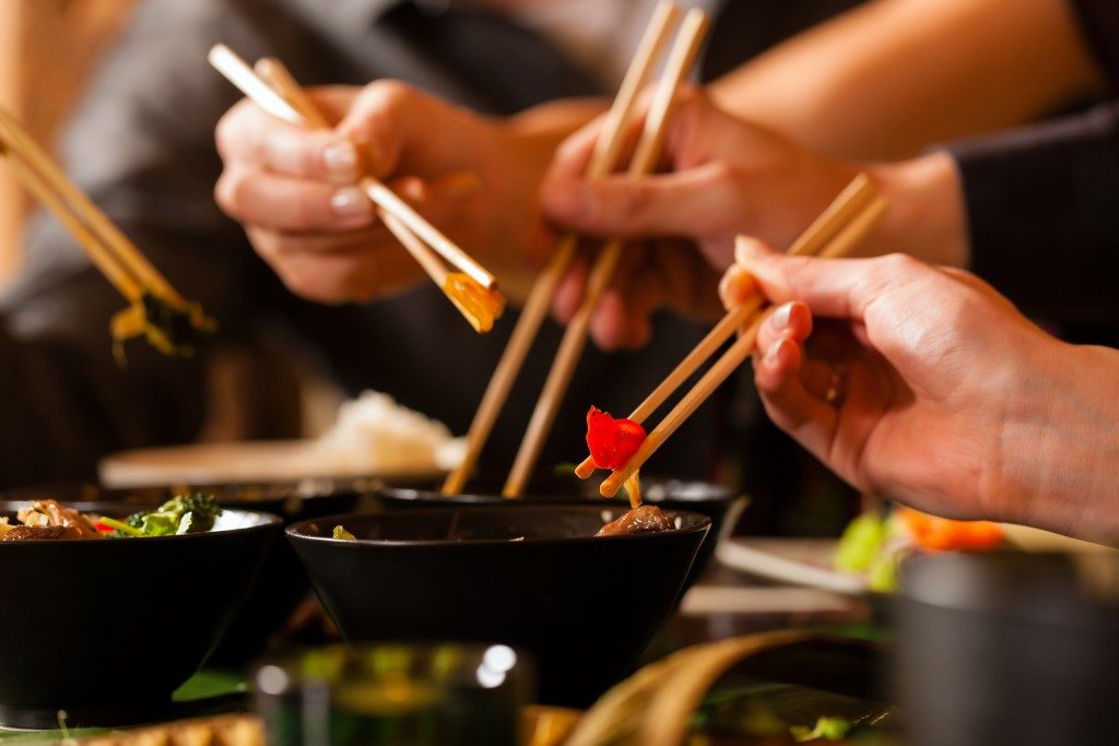 A group of people holding chopsticks