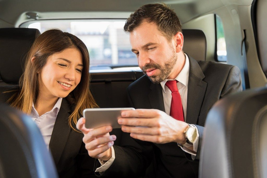 business people in the backseat of a car looking at phone