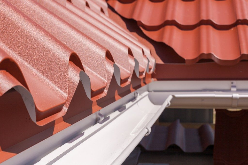 roof in red metal tile with white rain gutter