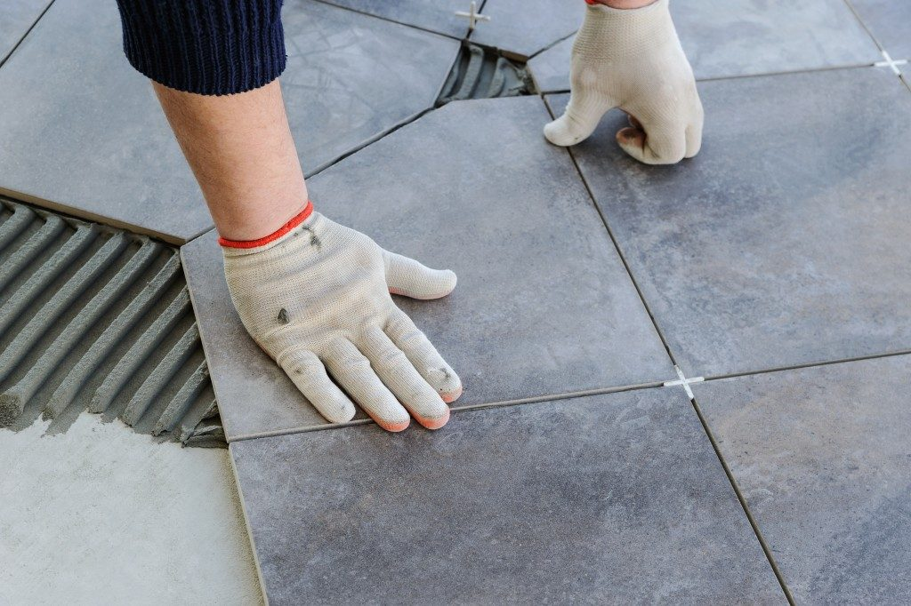 man placing ceramic tiles on the floor