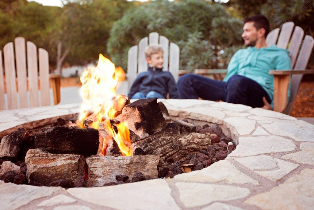Father and son hanging out near an outdoor firepit in their yard