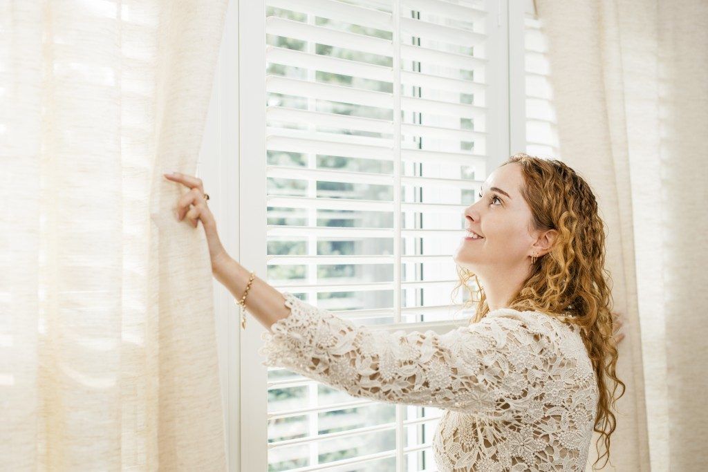 Happy woman looking out big bright window with curtains and shutters