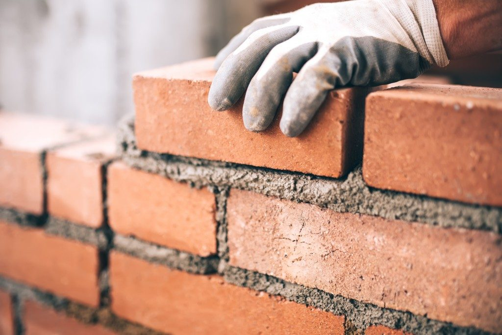 constuction worker stacking bricks
