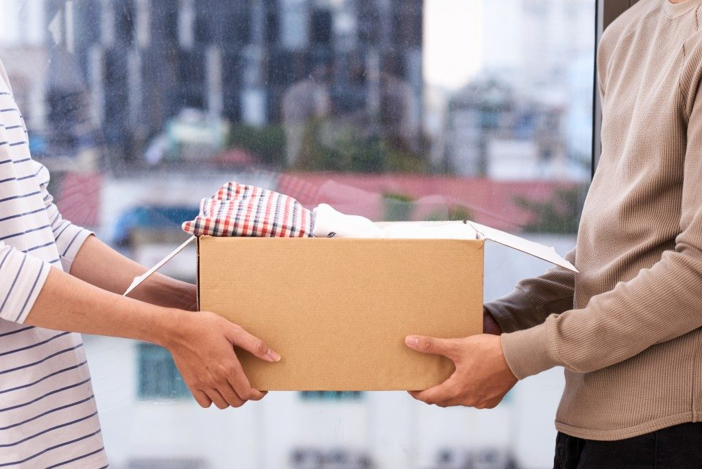 woman handing over a box of clothes to another person
