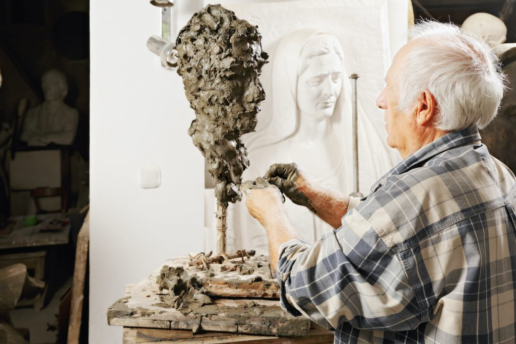 man sculpting a figure out of clay