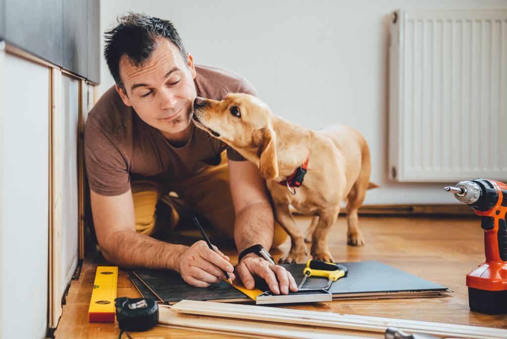 man renovating with dog